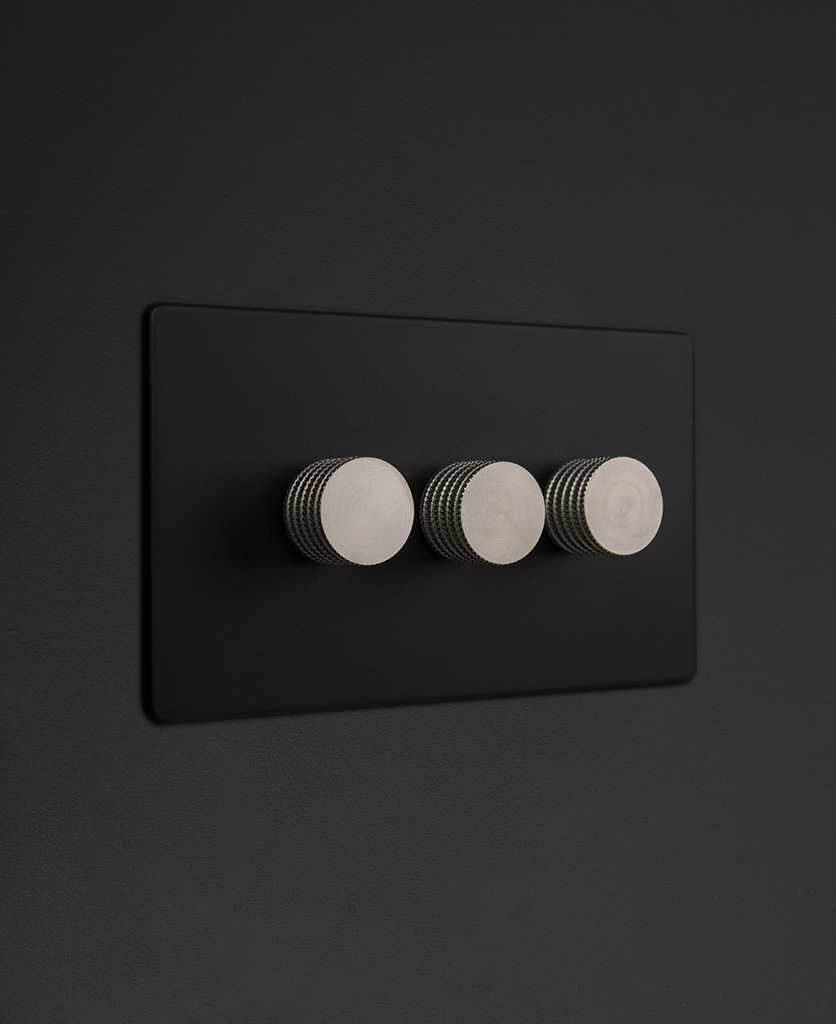 Black three gang dimmer switch with silver knobs on black background