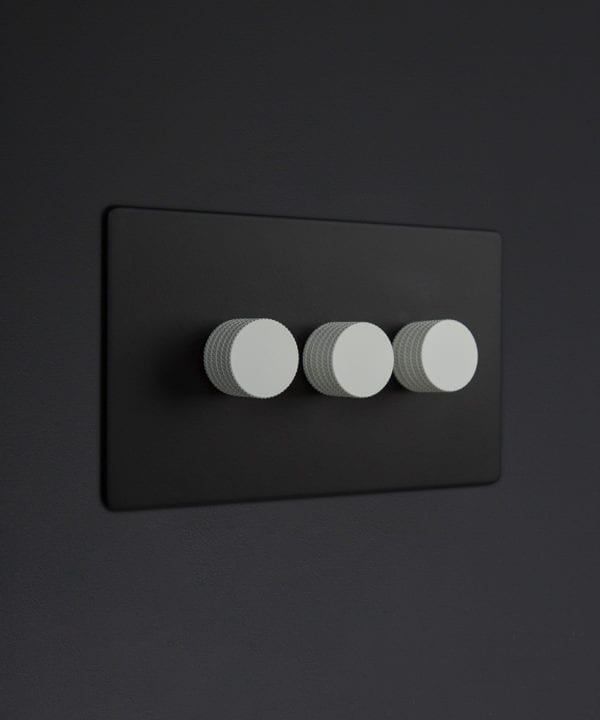 Black three gang dimmer switch with white knobs on black background