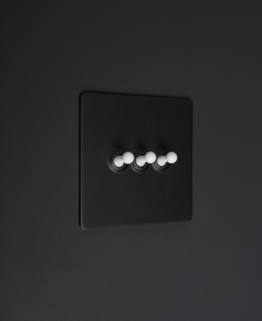 Black three gang toggle switch with white toggles on black background