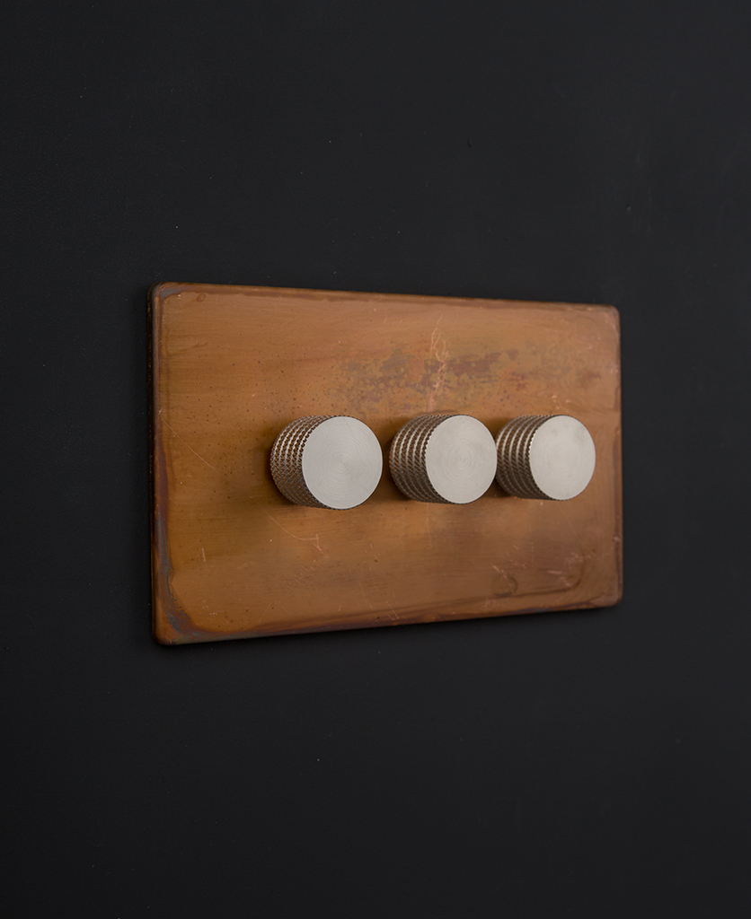 copper & silver triple dimmer on a black wall