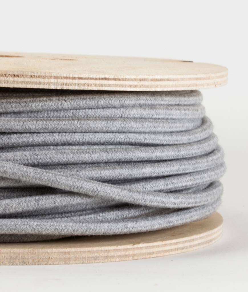closeup of felt grey fabric cable on reel against white background