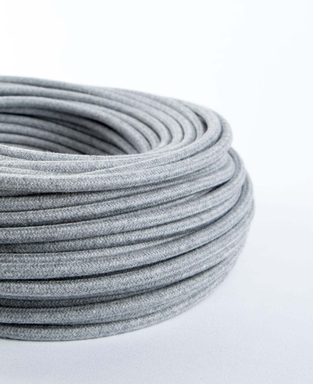 closeup of felt grey fabric cable coil against white background