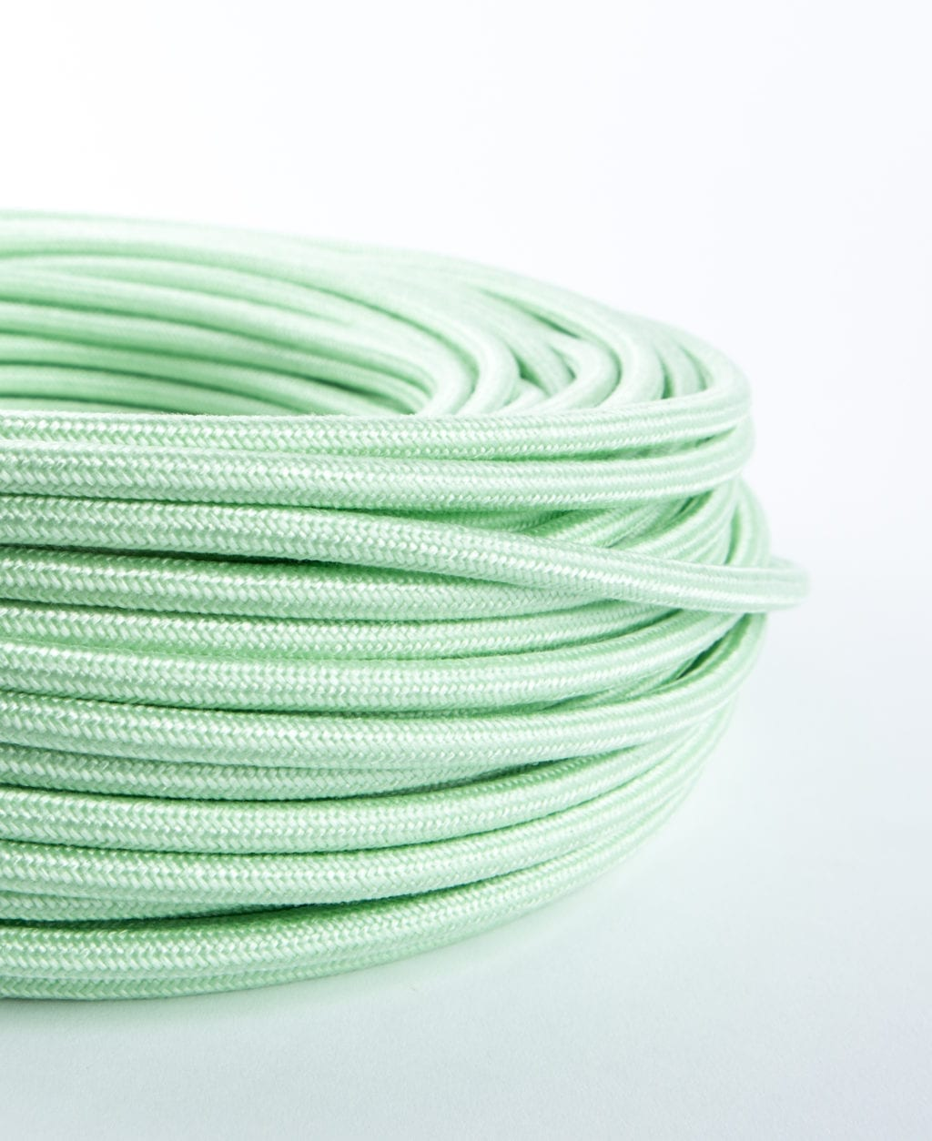 close up of mint green fabric cable coil on white background