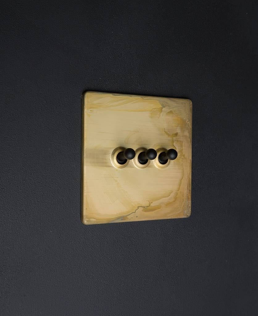 Smoked gold dolly light switches with black triple toggle detailingagainst black background