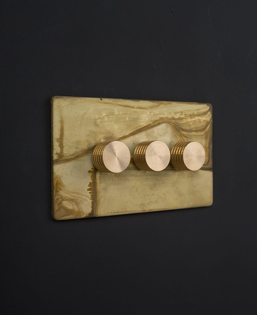 smoked gold & gold triple dimmer against black background