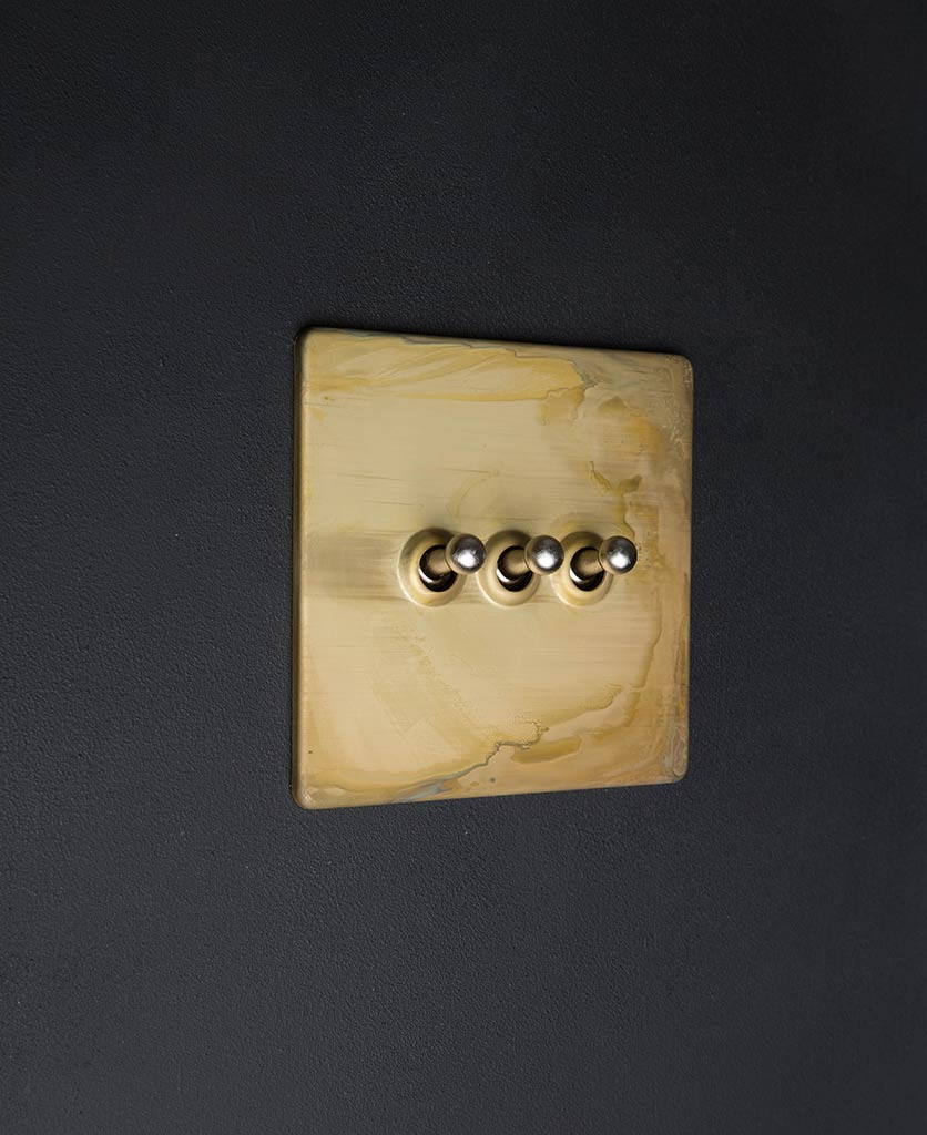 smoked gold and silver triple toggle switch against black backkground