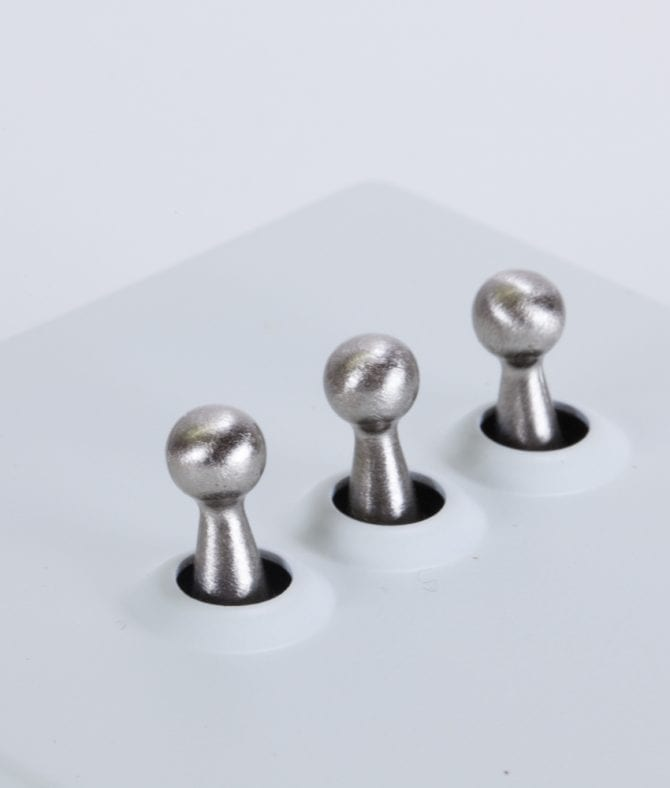 closeup of white and silver triple toggle switch against white background