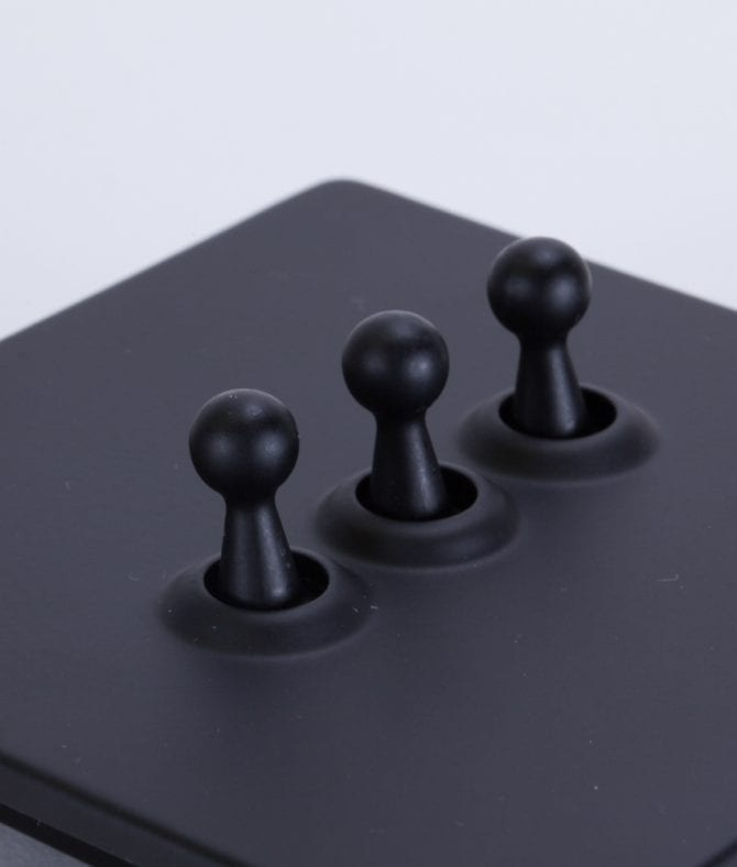 closeup of black and black triple toggle switch against white background