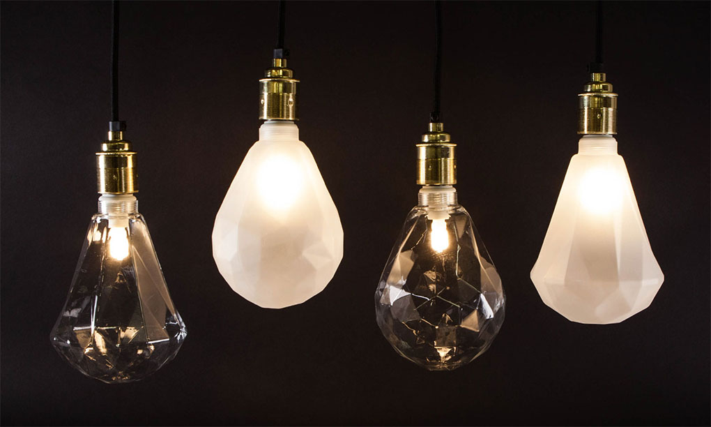 geometric light bulbs suspended from gold bulb holders against black background
