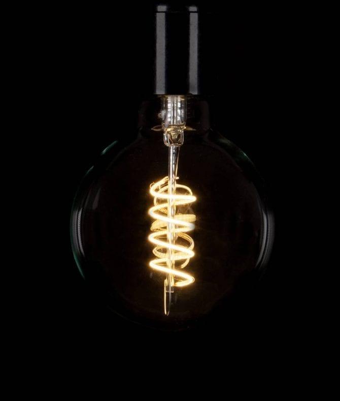 large globe spiral filament led light bulbs against black background