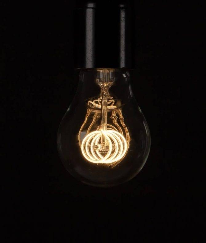 LED filament bulbs quad loop warm glow bulb against a black background