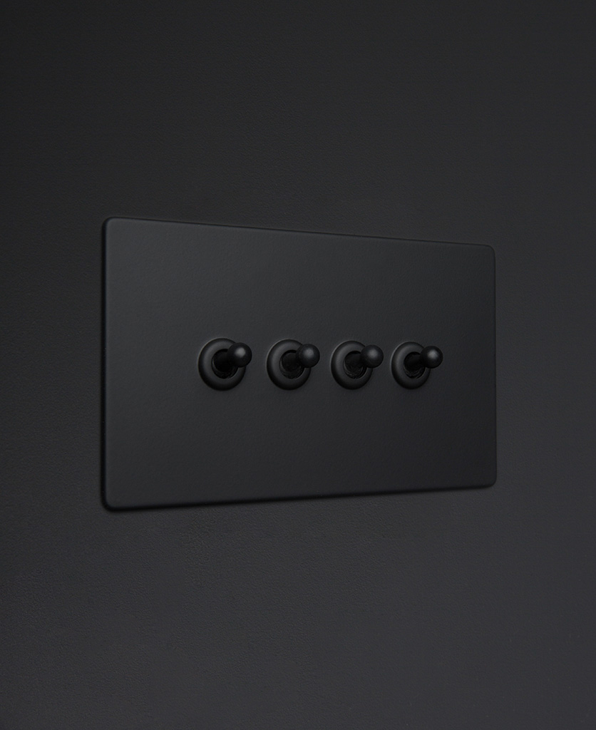 Black four gang toggle switch with black toggles on black background