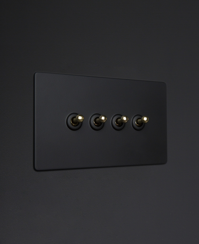Black four gang toggle switch with gold toggles on black background