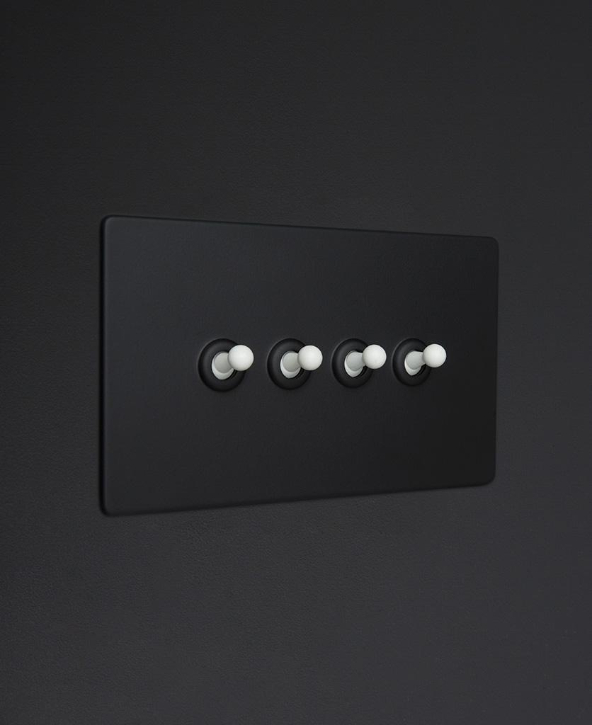 Black four gang toggle switch with white toggles on black background