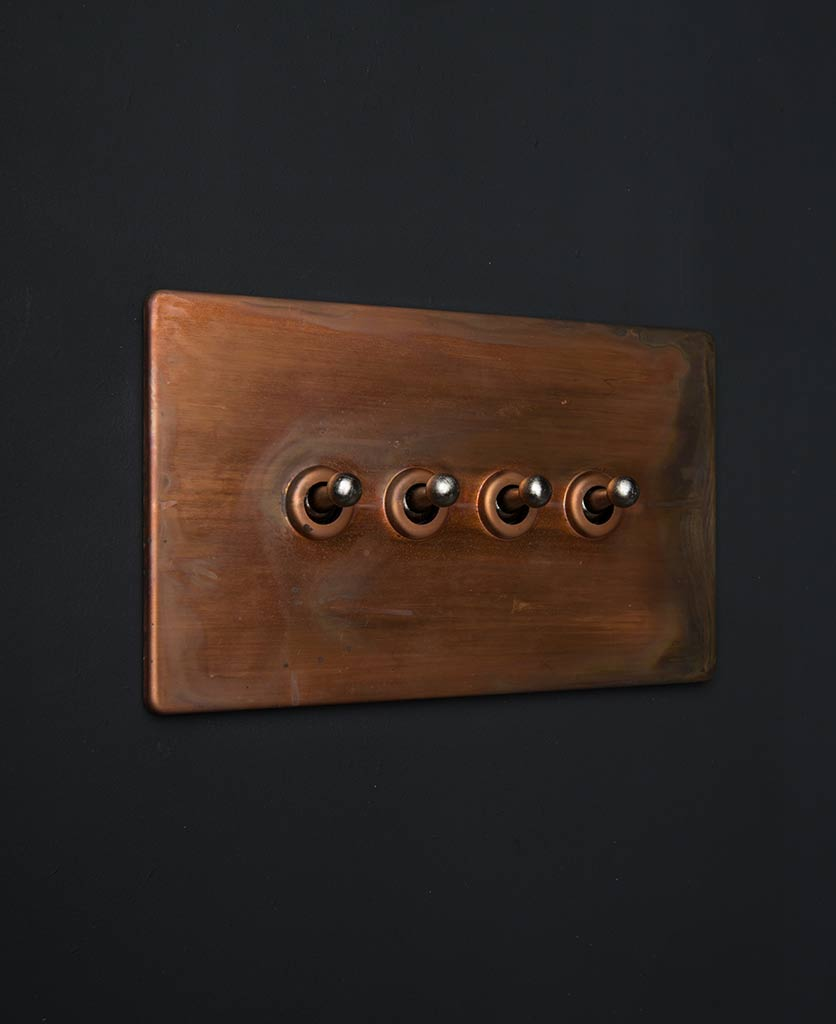 copper lamp switches with quadruple silver toggle detail against black background