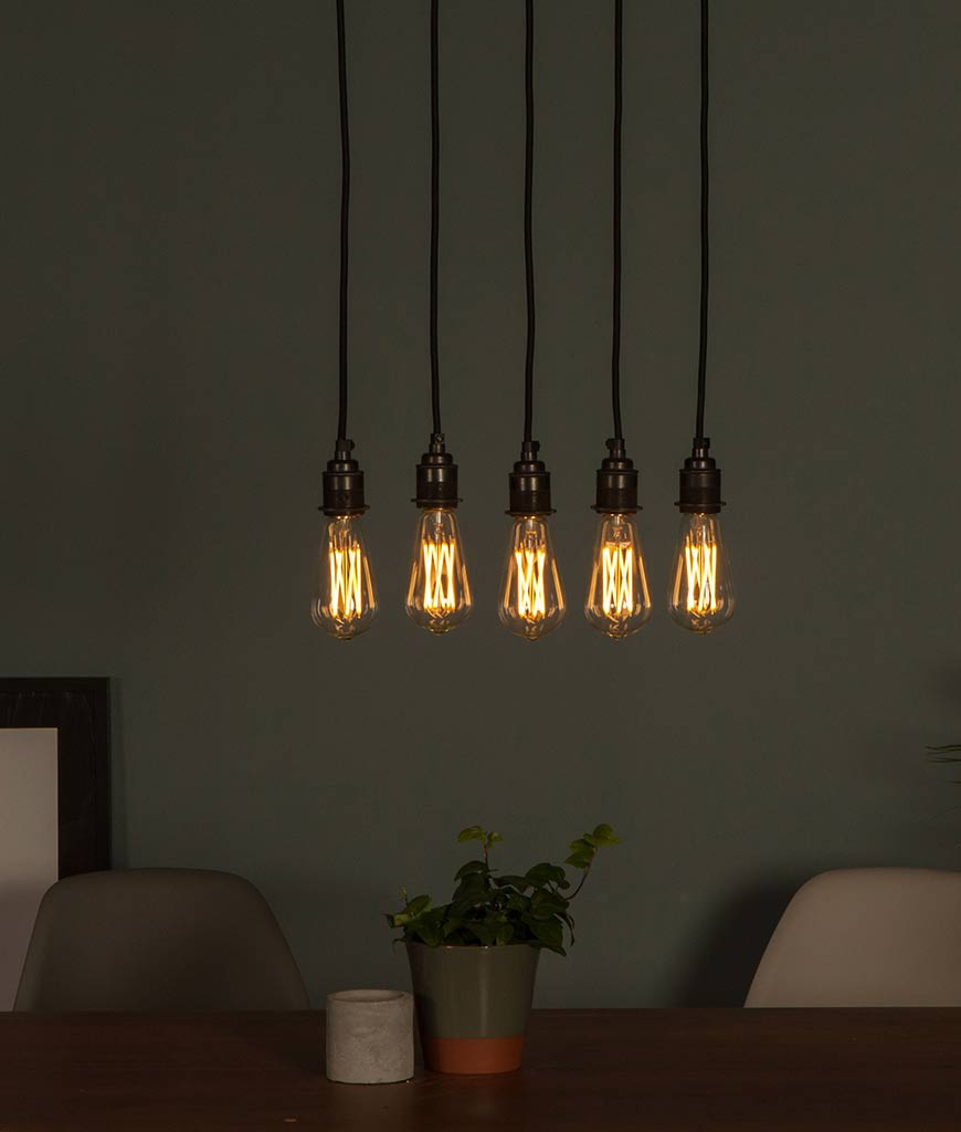 Large pear squirrel cage filament LED warm light bulbs suspended in a series above a table on dark grey background