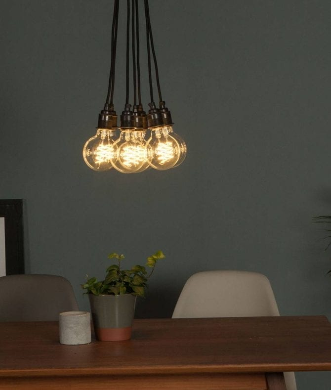 led globe bulb suspended in a cluster above a table against grey wall