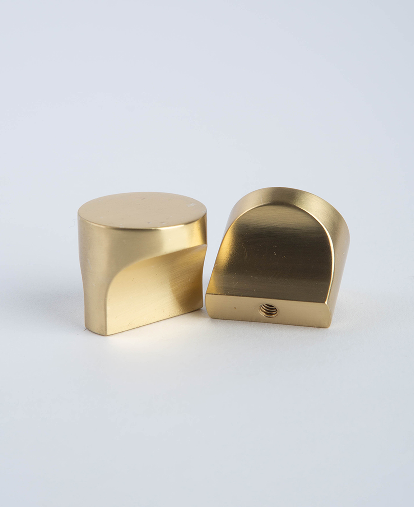 two brass abstract drawer knobs against white background