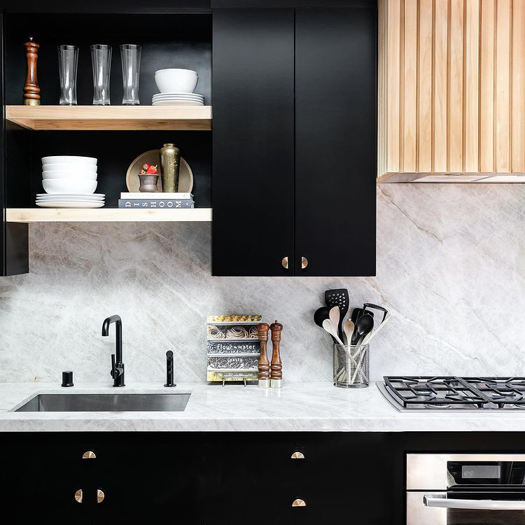 gold nouveau semi circular knobs on black cupboards in a black and white marble kitchen