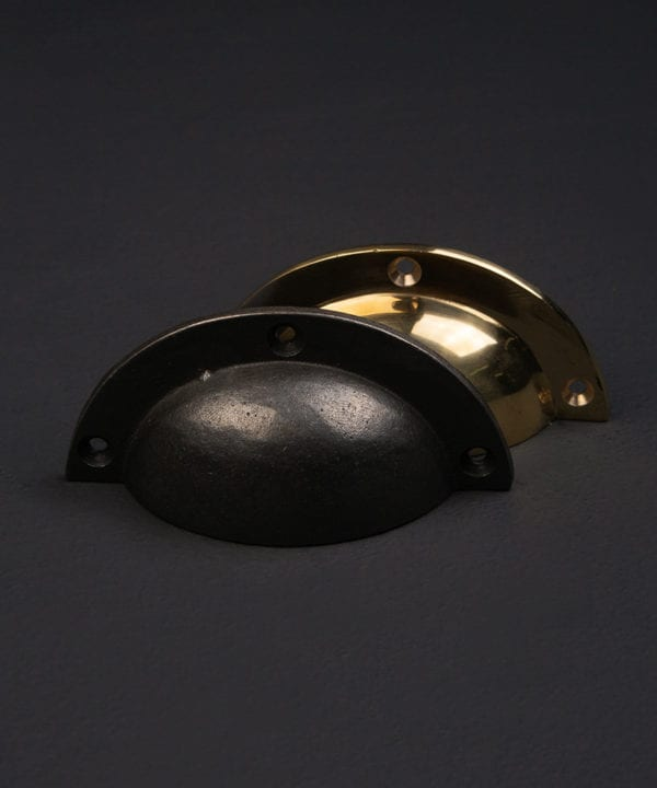 Bothy brass cup handles against a black background
