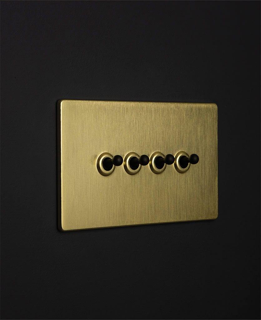 gold & black quad toggle switch against black background