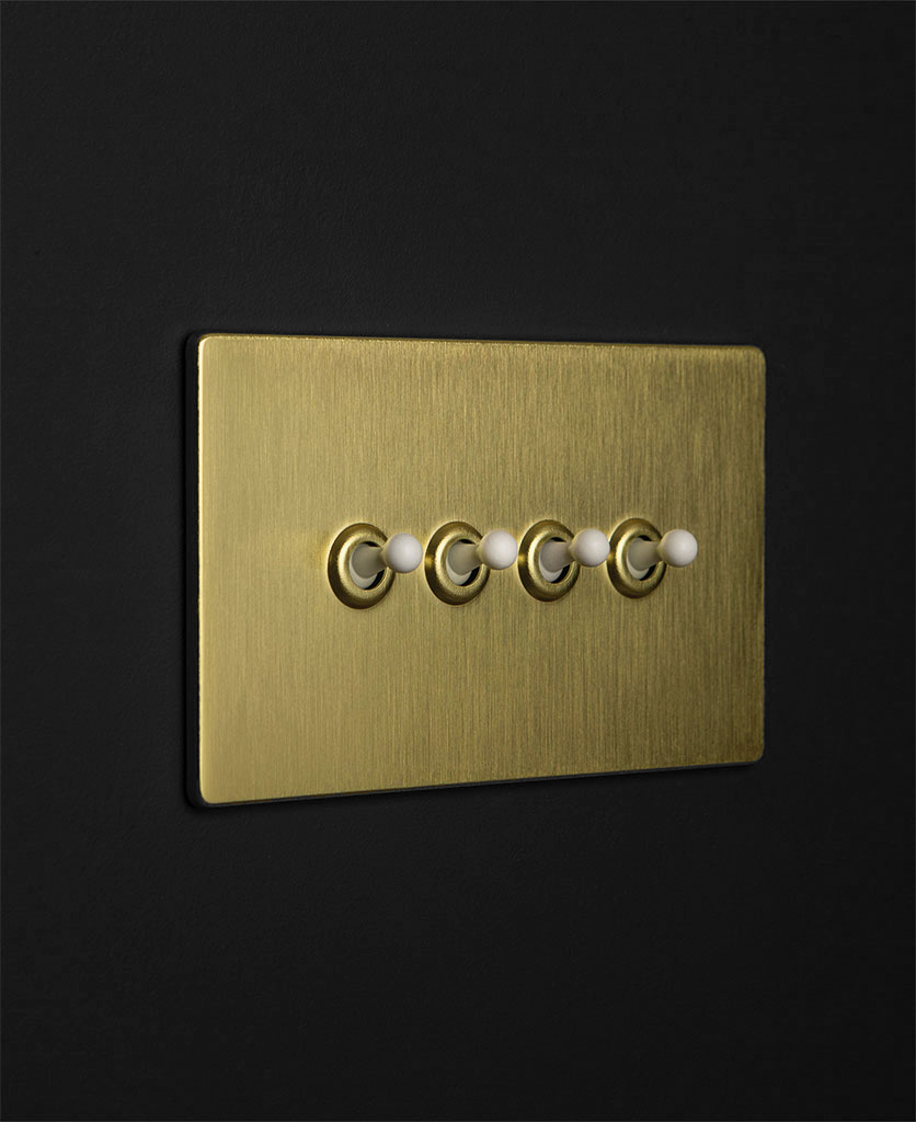 gold toggle light switch with four white toggle switches against black wall