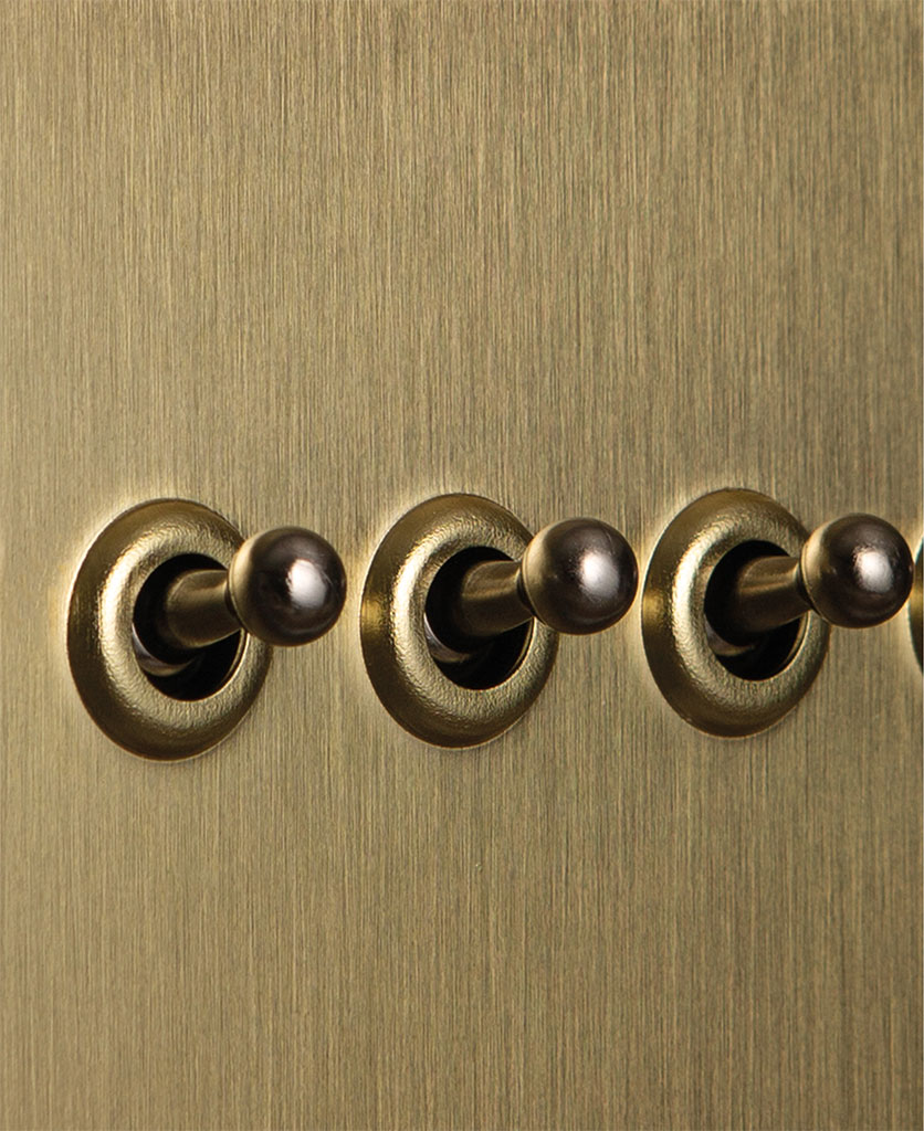 closeup of gold quadruple toggle switch with silver toggle detail