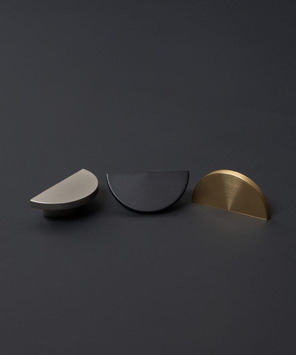 nouveau drawer pulls and knobs in black silver and brass against dark grey background