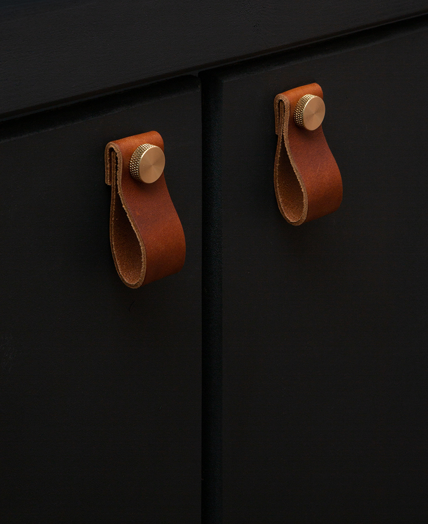 brown leather cupboard handles secured with a gold knurled knob on a black cupboard door