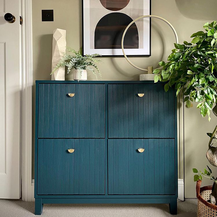 gold nouveau semi-circular knobs on dark blue painted cabinet in a soft green and white room