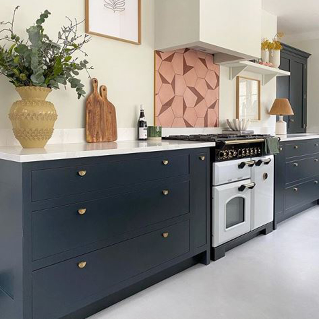 nouveau gold knobs on navy drawers in a white, pink and navy kitchen