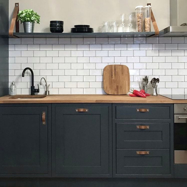thor leather handles on dark grey cupboards in white and grey kitchen