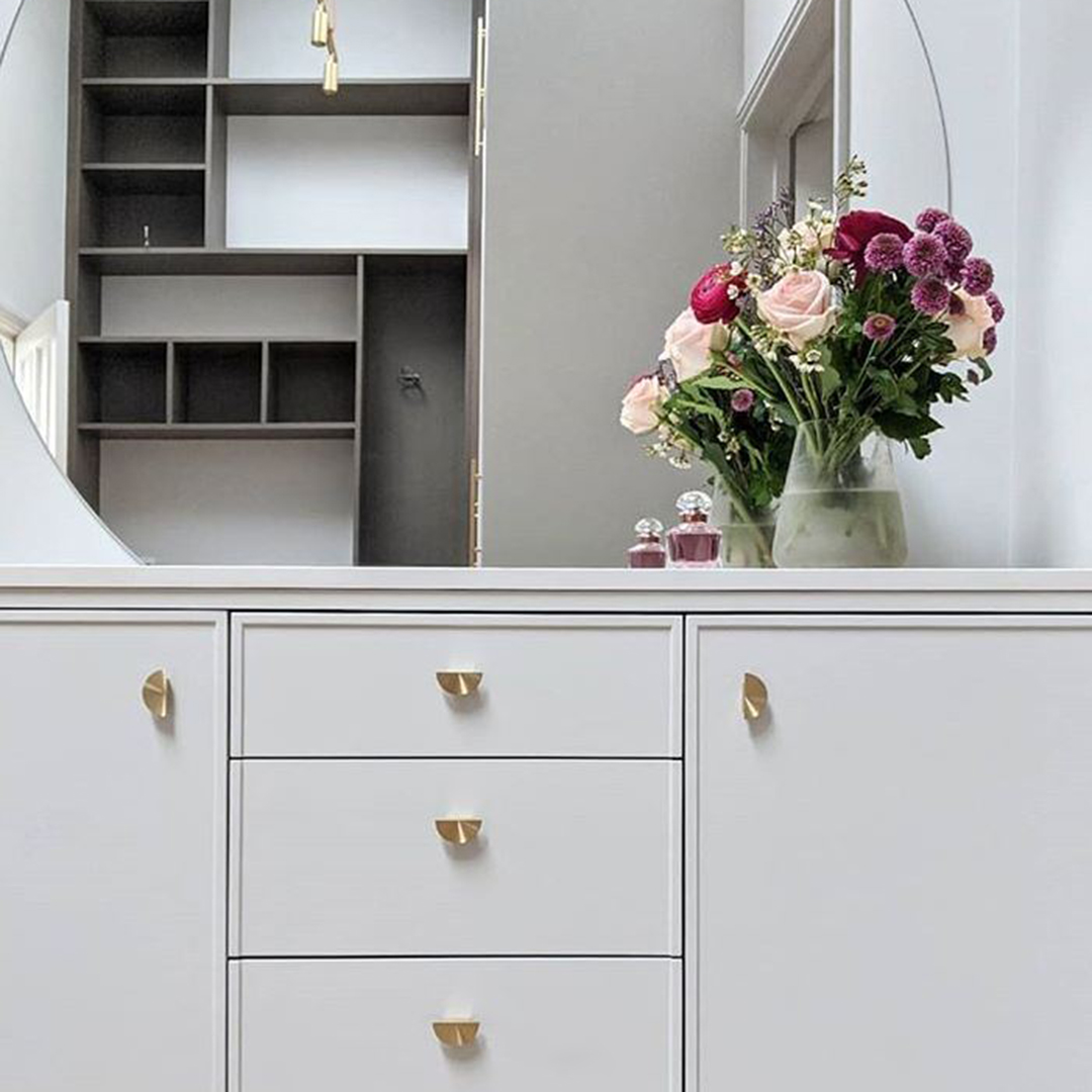 nouveau brass drawer handles on white unit in a bedroom