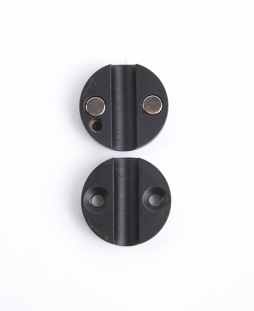 black magnetic cable guide against white background