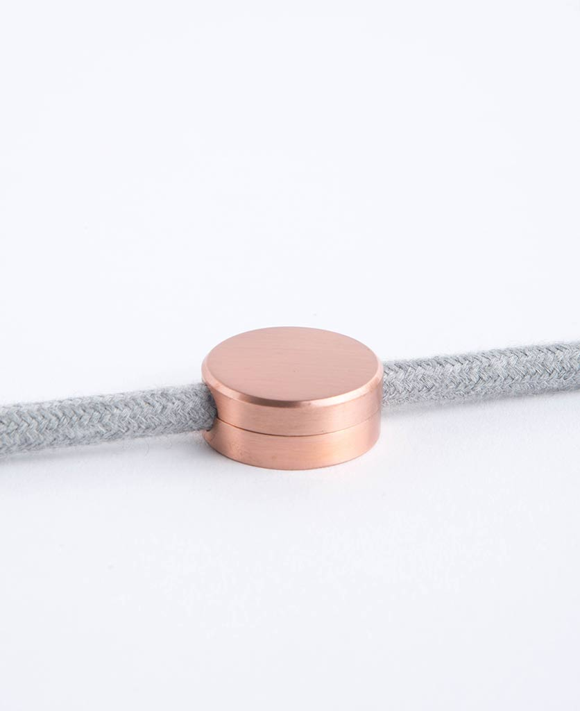 copper magnestic cable guide with felt grey fabric cable against white background
