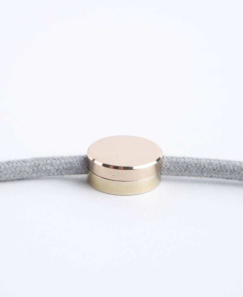 gold magnetic cable guide with felt grey fabric cable against white backkground