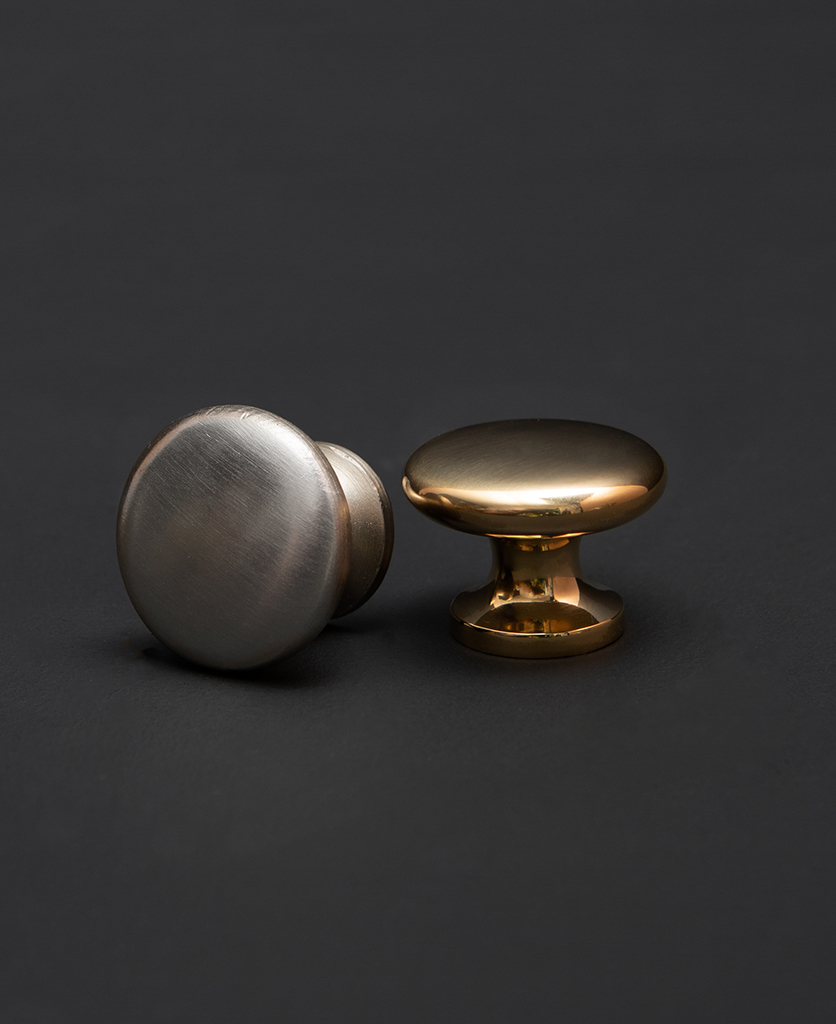 realist drawer knobs, gold and silver circular knobs against a black backdrop