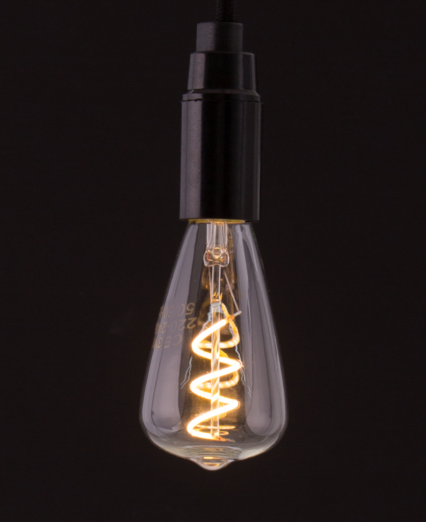 pear shaped LED E14 bulbs with spiral filament against black background