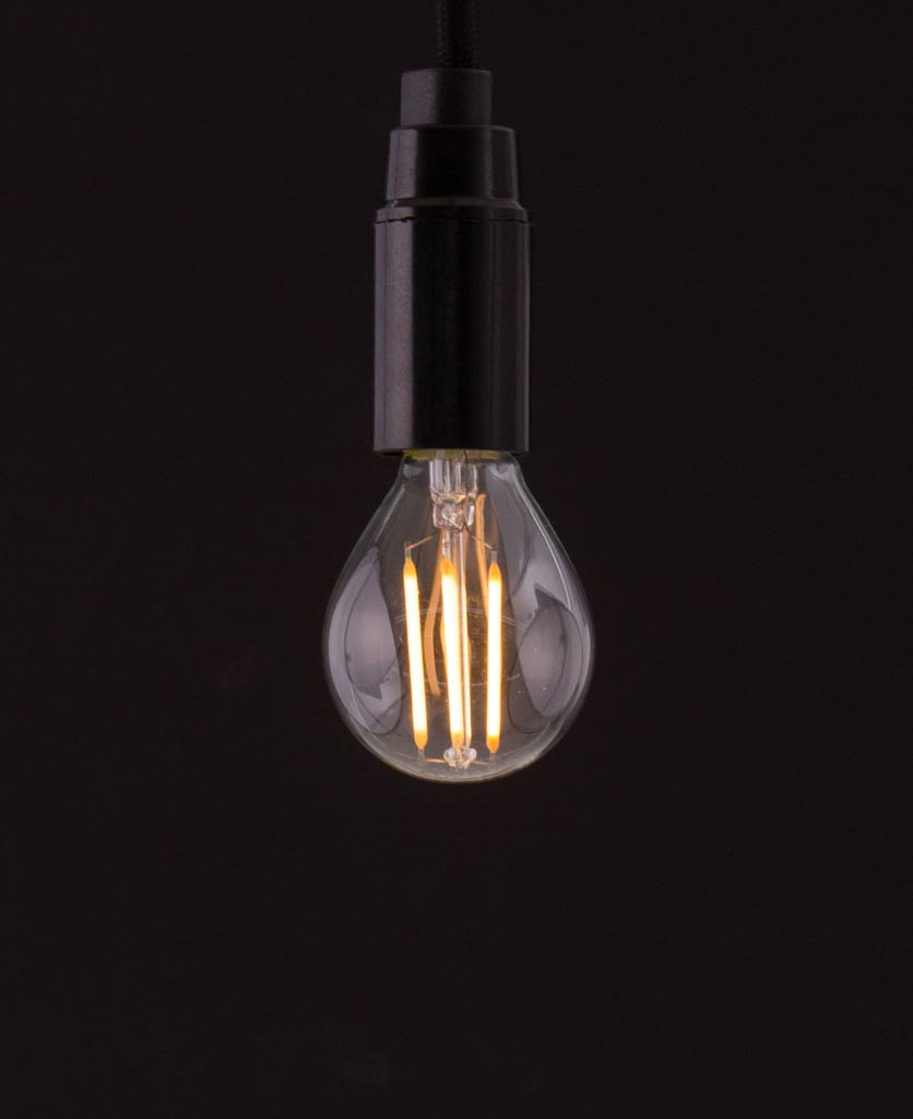 E14 LED bulb with squirrel cage filament against black background