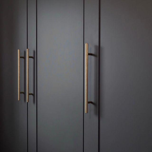 gold skyscraper knurled handle on dark grey cupboards