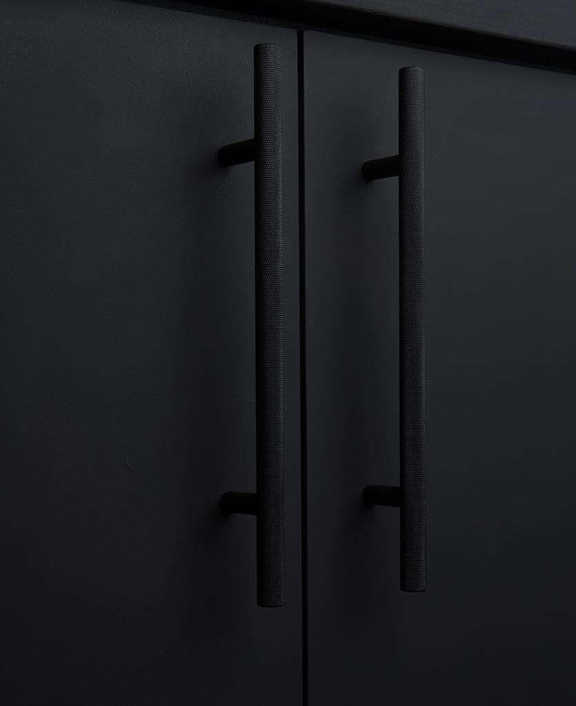 black knurled door handles on black cupboard
