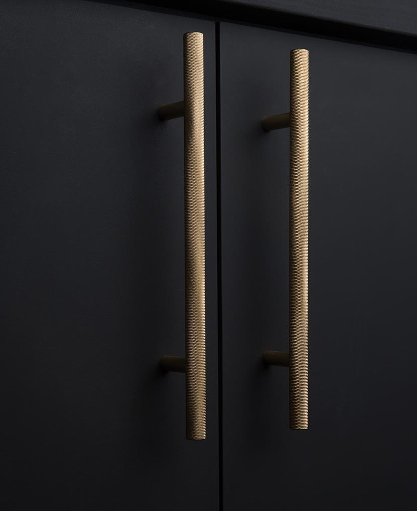 gold knurled door handles on black cupboard
