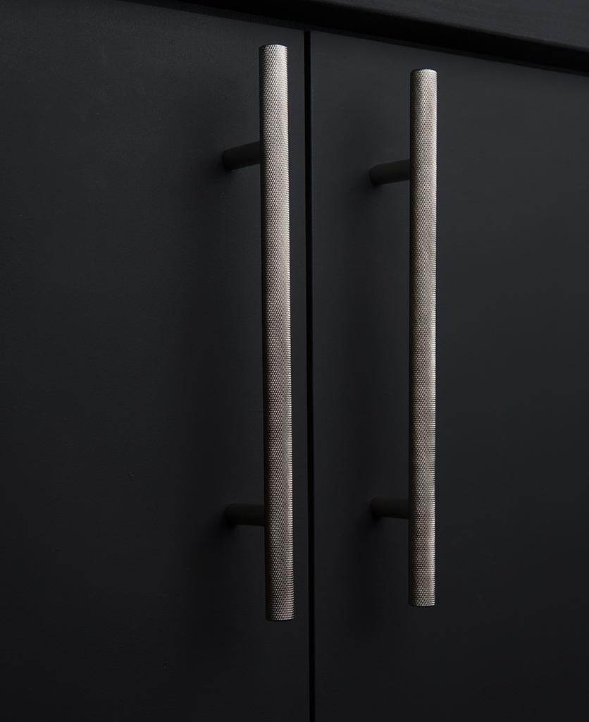 silver knurled door handles on black cupboard