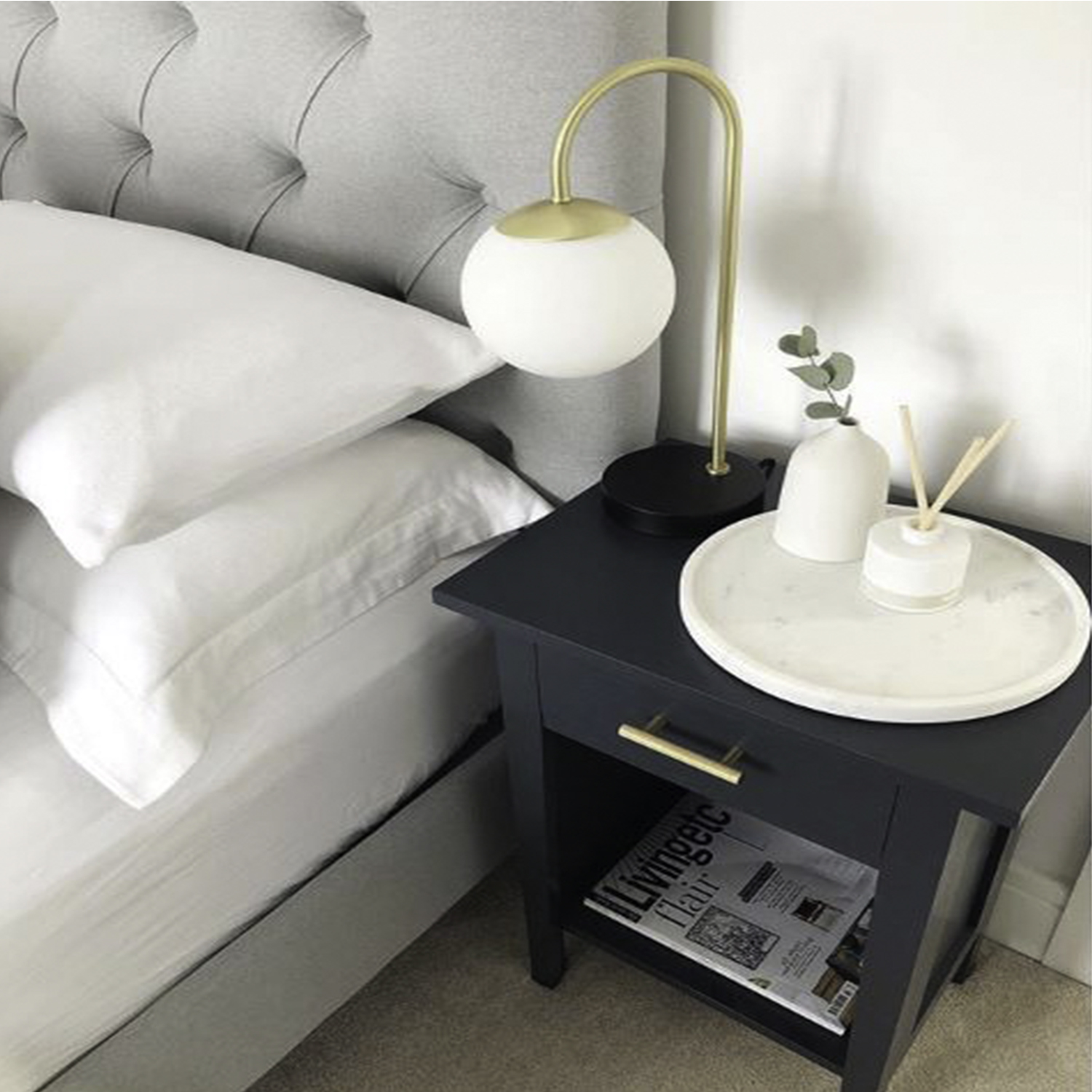 brass skyscraper handle on dark grey bedside table in a white and grey bedroom