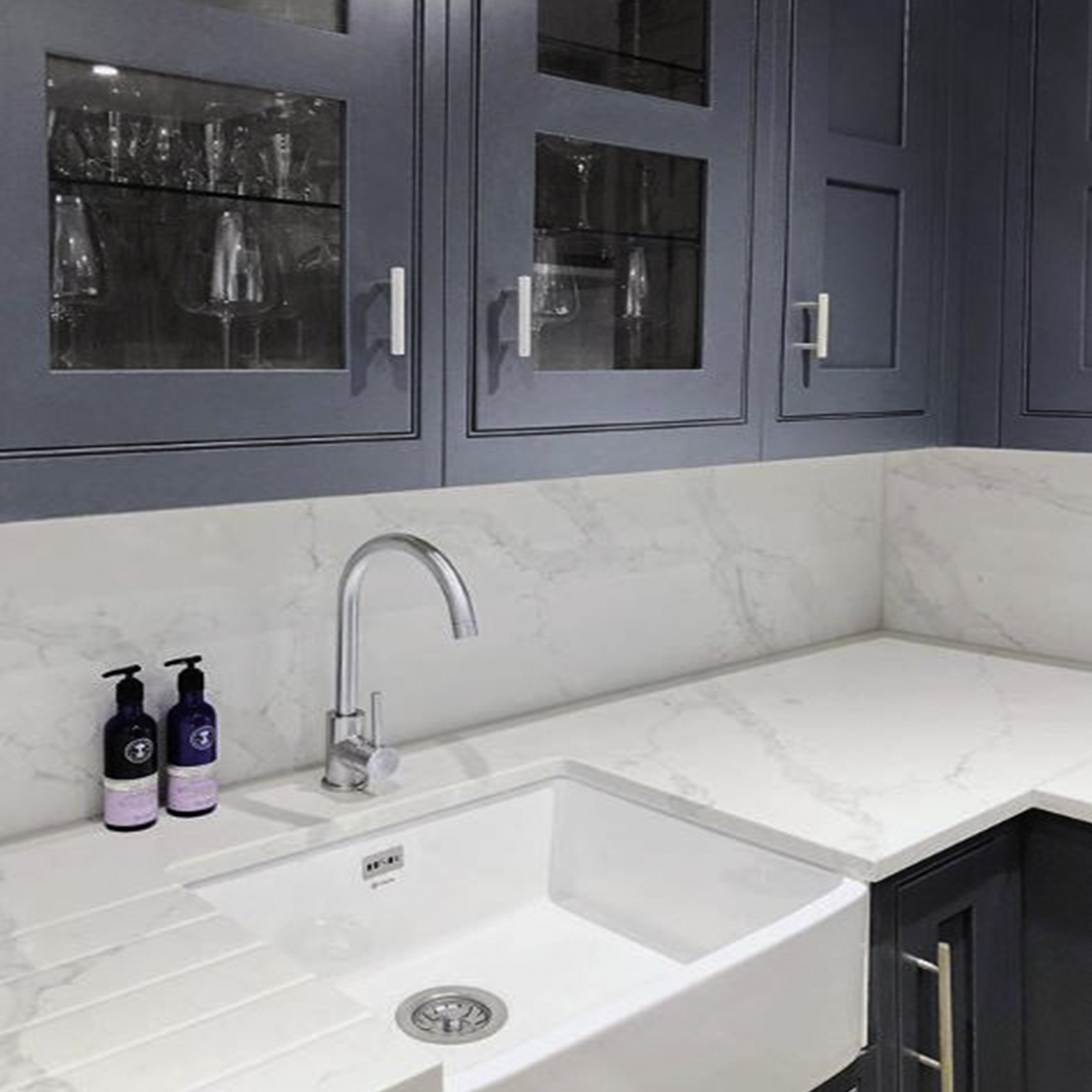 skyscraper silver handle on dark blue cupboards in a blue and white marble kitchen