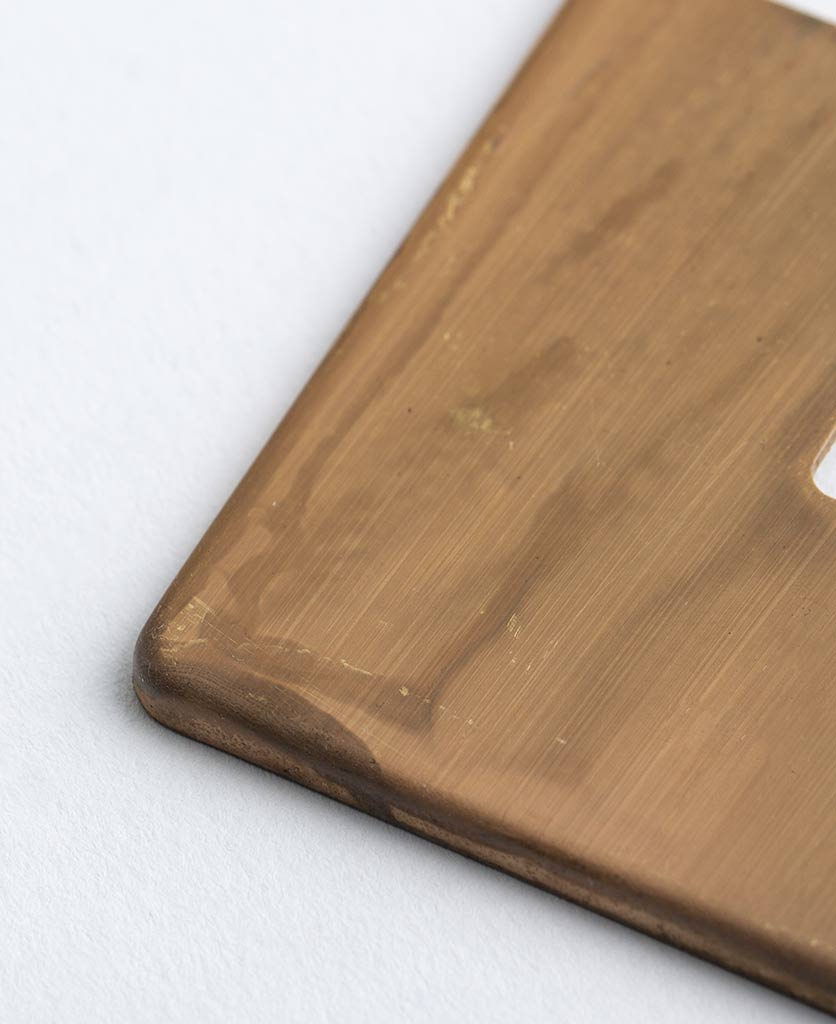 closeup of smoked gold plate against white background