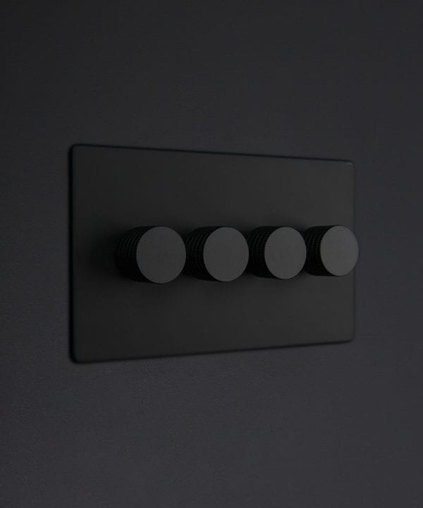 Black four gang dimmer switch with black knobs on black background