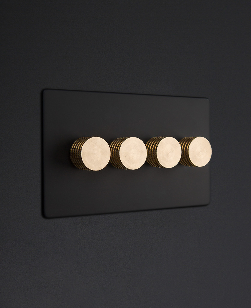 Black four gang dimmer switch with gold knobs on black background