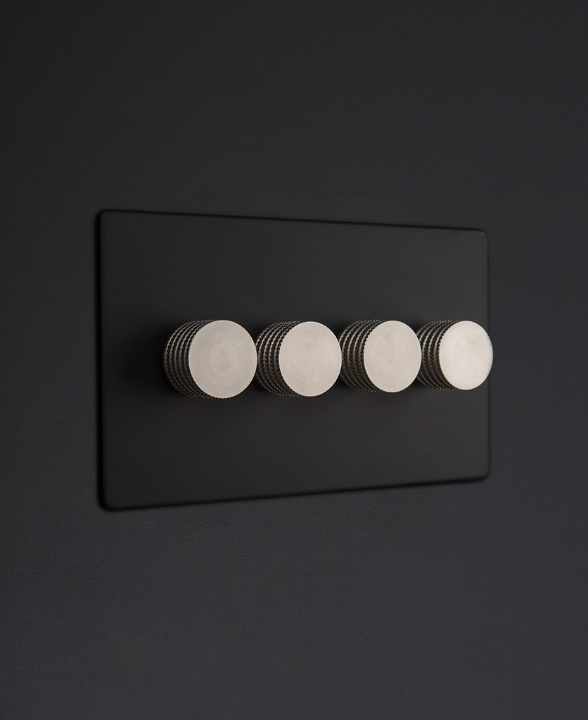 Black four gang dimmer switch with silver knobs on black background