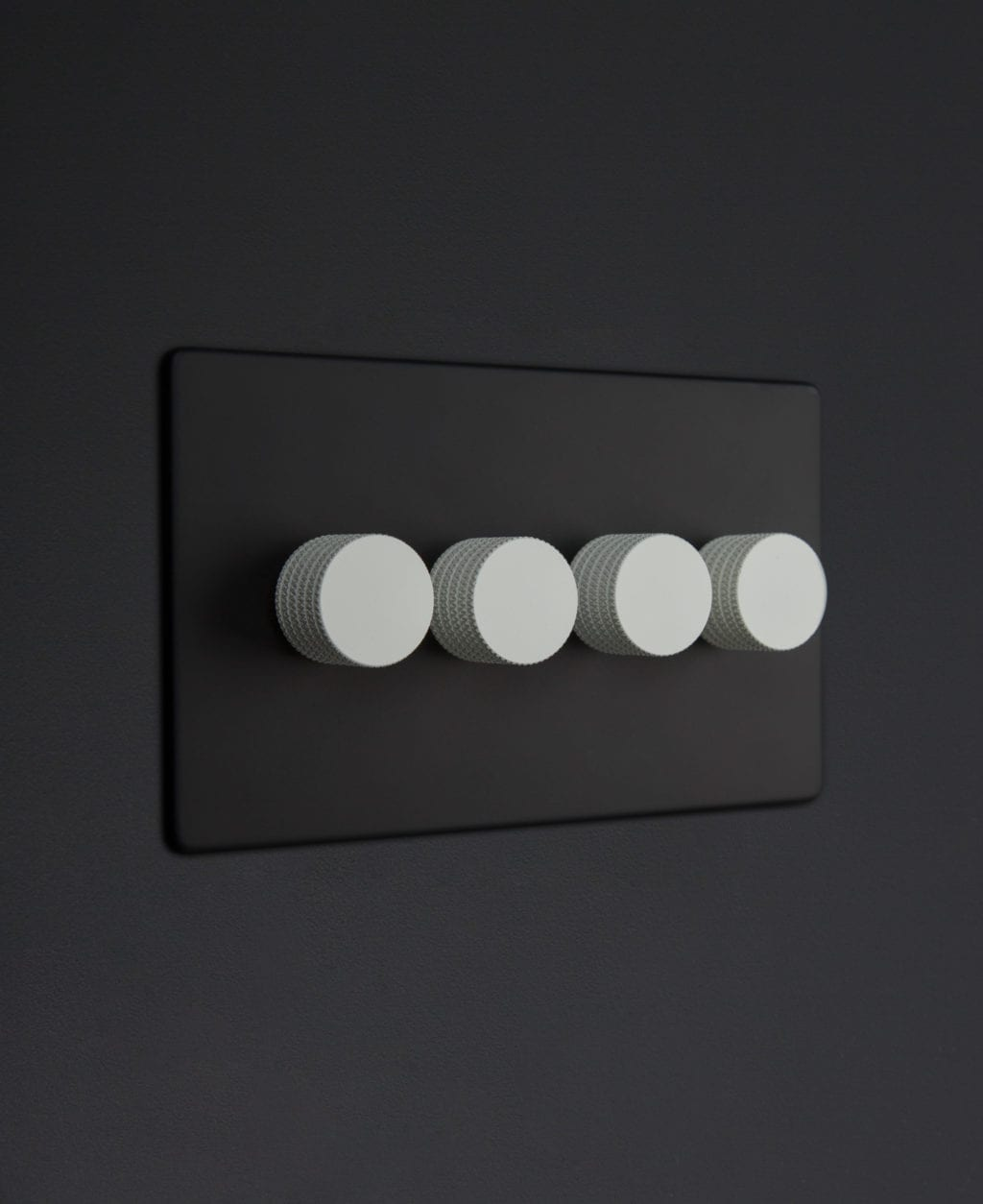 Black four gang dimmer switch with white knobs on black background